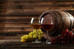 Glas Rot und Weißwein mit Trauben auf dem braunen hölzernen Hintergrund Lizenzfreie Stockbilder