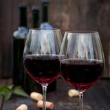 Glas Rotwein auf altem Holztisch Stockbilder