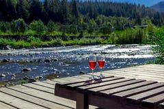 Glas Rotwein auf dem Hintergrund von einem Gebirgsfluss Hölzerner Wagenaufenthaltsraum, Berge, Luxusfeiertag lizenzfreies stockbild