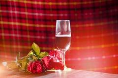 Glas Rotwein auf des romantischen dem romantischen Gedeck Liebes-Konzeptes des Bar Valentinsgrußabendessens verziert mit Champagn lizenzfreies stockfoto