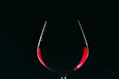 Glas Rotwein auf dunklem Hintergrund Stockfotos