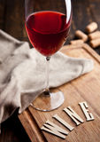 Glas Rotwein auf hölzernem Brett mit Buchstaben und Korken Lizenzfreies Stockfoto