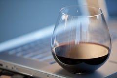 Glas Rotwein auf Laptop lizenzfreies stockbild