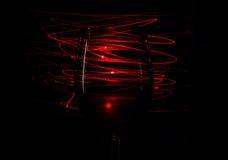 Glas Rotwein auf Streifen eines roten Hintergrundzusammenfassungs-Lichtes auf schwarzem Hintergrund Stockbild