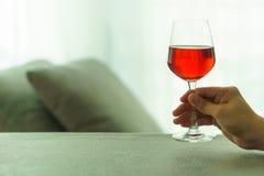 Glas Rotwein, der gehalten wird Stockbild
