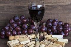 Glas Rotwein, Korken und Trauben stockbild