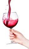 Glas Rotwein mit spritzt in der Hand lokalisiert Lizenzfreie Stockfotos
