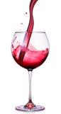 Glas Rotwein mit spritzt lokalisiert auf einem Weiß Lizenzfreie Stockbilder