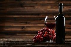 Glas Rotwein mit Trauben auf dem braunen hölzernen Hintergrund Stockbilder