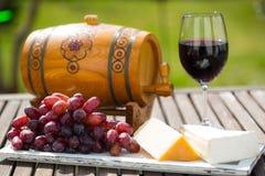 Glas Rotwein, Trauben und Käse auf einem Behälter im Garten Lizenzfreie Stockbilder