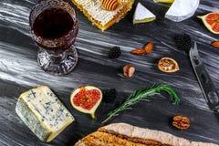 Glas Rotwein und Käse mit Stücken schimmeliger Käse, Prosciutto, Feigen, Honig, Nüsse auf schwarzem Schieferhintergrund stockfotos