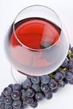 Glas Rotwein und purpurrote Trauben Stockfotos