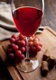 Glas Rotwein und Trauben auf hölzernem Brett Stockbilder