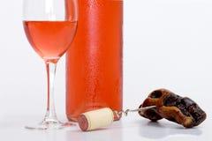 Glas roze wijn met fles en kurketrekker royalty-vrije stock afbeeldingen