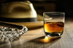 Glas of rum in a bar in Cuba. Glas of rum, cigar and a panama hat in a bar in Cuba royalty free stock photography