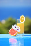 Glas Saft und Blumen auf einem Pool lizenzfreie stockfotos