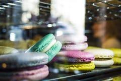 Glas show-venster met verlichting in koffiewinkel met multi-colored Franse macarons Smakelijke snoepjes Cake stock foto