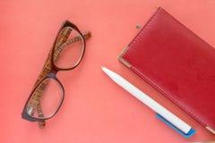 Glas-, Stift- und NotizbuchGeschäftsfrau-Zeitplankonzepthintergrund stockbild