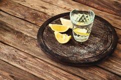 Glas Tequila mit Zitronenscheiben auf einem hölzernen Hintergrund Lizenzfreies Stockfoto