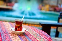 Glas traditioneller türkischer Tee auf dem Tisch mit Farbhintergrund Stockfotos