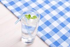 Glas Trinkwasser mit Minze auf einer Tabelle bedeckt mit einem Kontrolleur lizenzfreie stockfotos