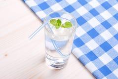Glas Trinkwasser mit Minze auf einer Tabelle bedeckt mit einem Kontrolleur stockfotos