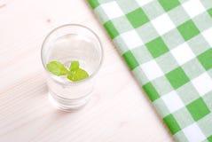 Glas Trinkwasser mit Minze auf einer Tabelle bedeckt mit einem Kontrolleur lizenzfreies stockfoto