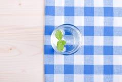 Glas Trinkwasser mit Minze auf einer Tabelle bedeckt mit einem Kontrolleur stockfoto