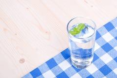 Glas Trinkwasser mit Minze auf einer Tabelle bedeckt mit einem Kontrolleur stockbilder