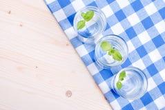 Glas Trinkwasser mit Minze auf einer Tabelle bedeckt mit einem Kontrolleur stockfotografie
