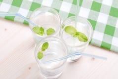 Glas Trinkwasser mit Minze auf einer Tabelle bedeckt mit einem Kontrolleur stockbild