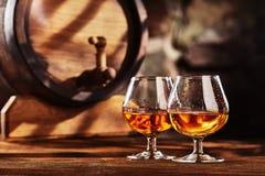 Glas twee van Cognac en oud eiken vat defocussed stock afbeeldingen