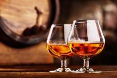 Glas twee van Cognac en oud eiken vat defocussed royalty-vrije stock afbeeldingen