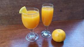 glas twee vers jus d'orange en één oranje fruit op de bruine houten lijst stock foto