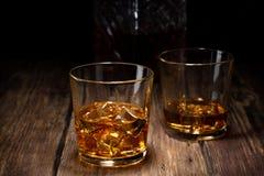Glas twee whisky met ijs en kristalkaraf stock foto
