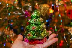 Glas uitstekende stuk speelgoed groene Kerstboom op de open palm van hand Stock Afbeeldingen