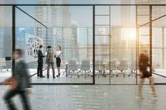 Glas ummauerte Büro mit Leuten und einem Plakat Lizenzfreie Stockbilder