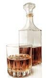 Glas und Dekantiergefäß mit Alkohol auf einem weißen Hintergrund mit refle Stockfotografie