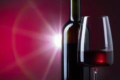 Glas und Flasche Rotwein auf dunklem Hintergrund Stockbilder