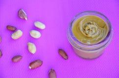 Glas und L?ffel der Erdnussbutter und der Erdn?sse auf purpurrotem Hintergrund von der Draufsicht Kopieren Sie Platz stockfotografie