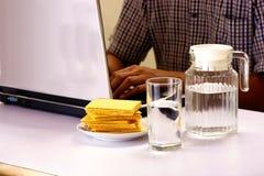 Glas und Pitcher Wasser und ein Stapel von den Crackern und von Mann, die an einer Laptop-Computer im Hintergrund arbeiten Stockbild