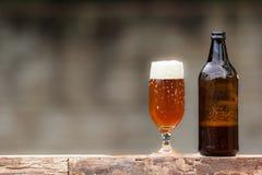Glas van bier en fles op houten lijst Stock Foto's