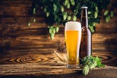 Glas van bier en fles op oude houten lijst Stock Afbeeldingen