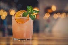 Glas van bier in pubGlass van cocktail met sinaasappel en munt in een club royalty-vrije stock afbeeldingen