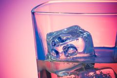 Glas van drank met ijs op disco violet licht Royalty-vrije Stock Foto