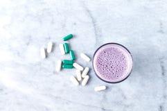 Glas van Eiwitschok met melk en bosbessen, b?ta-Alanine en l-Carnitine capsules op achtergrond Sporten die nutriti bodybuilding royalty-vrije stock fotografie