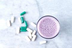 Glas van Eiwitschok met melk en bosbessen, b?ta-Alanine en l-Carnitine capsules op achtergrond Sporten die nutriti bodybuilding stock afbeelding