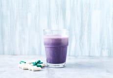Glas van Eiwitschok met melk en bosbessen, b?ta-Alanine en l-Carnitine capsules op achtergrond Sporten die nutriti bodybuilding stock foto's