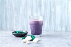 Glas van Eiwitschok met melk en bosbessen, b?ta-Alanine en l-Carnitine capsules op achtergrond Sporten die nutriti bodybuilding royalty-vrije stock afbeelding