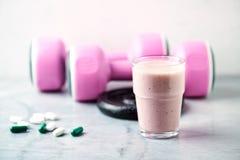 Glas van Eiwitschok met melk en frambozen BCAA-aminozuren, L - Carnitine capsules en roze domoren op achtergrond Sport stock afbeelding